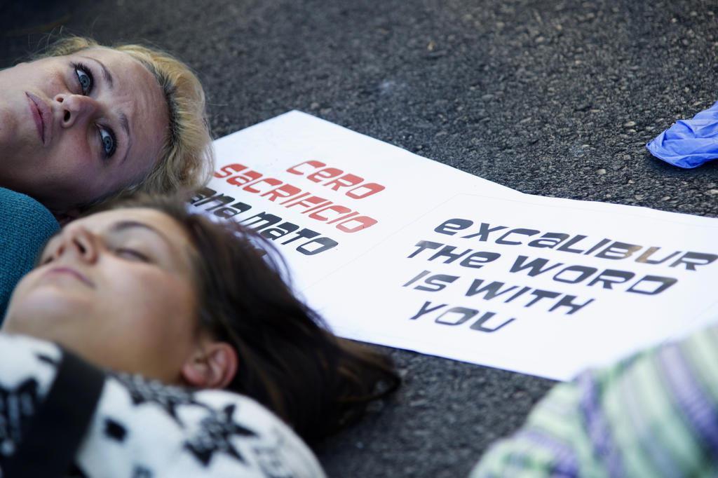 """Manifestantes carregavam cartazes com os dizeres """"Excalibur, o mundo está com você"""" Foto: Curto De La Torre/AFP"""