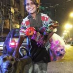 Menino de rua empresta seu agasalho para cachorro se esquentar em noite fria